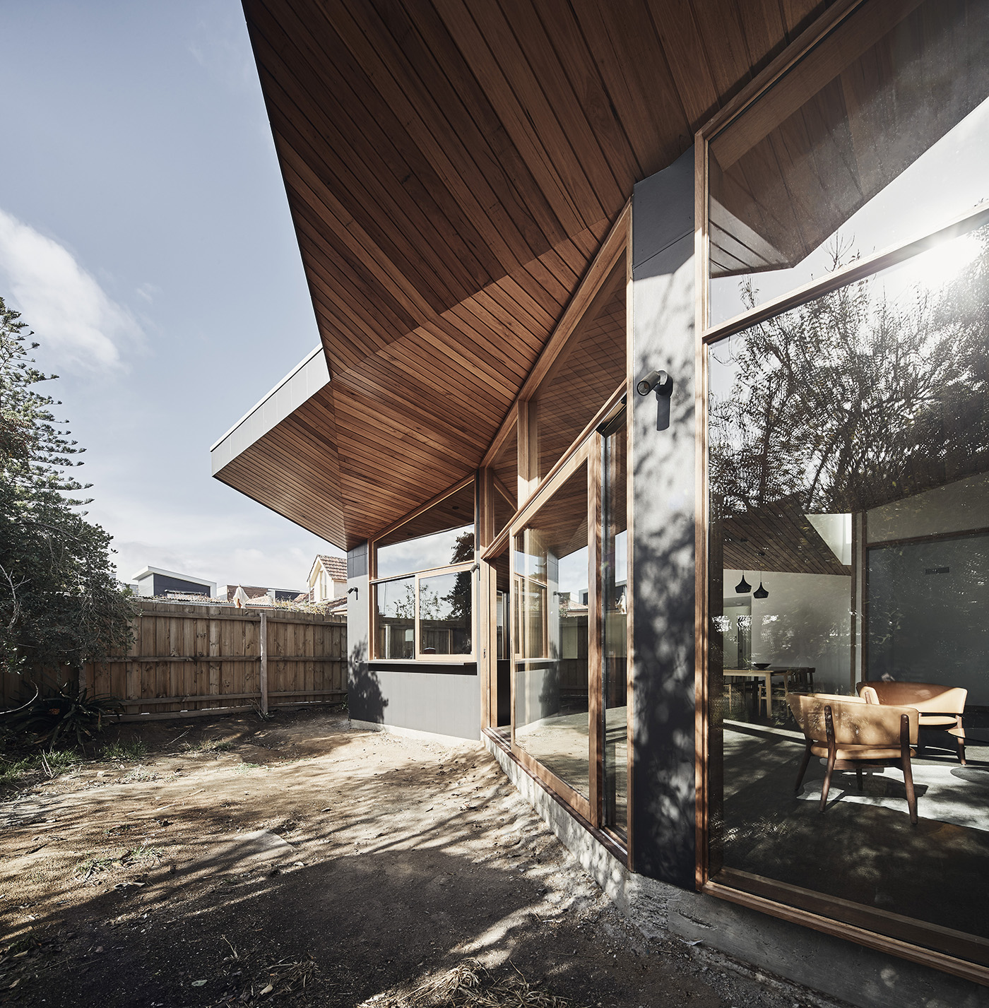 Contemporary architectural house facade facing a garden with facetted wood and glass
