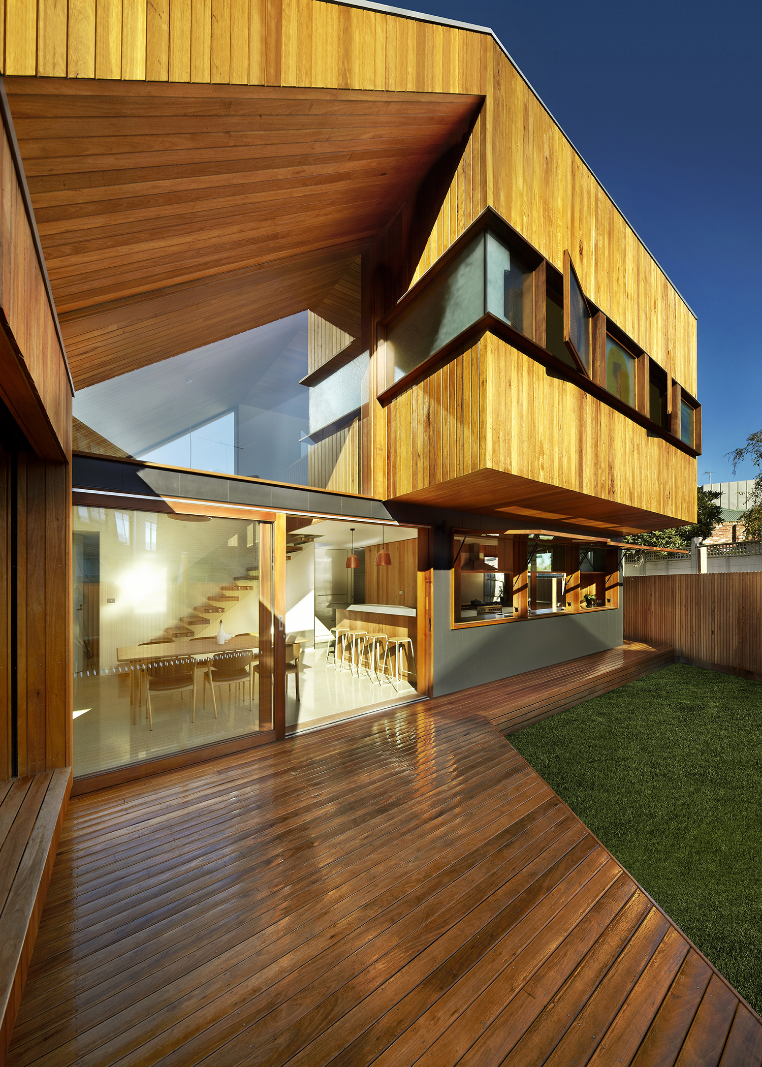 Timber clad house with double height living space and north facing deck